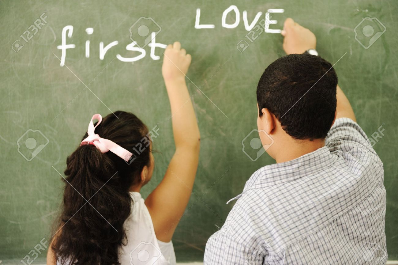 First Love - Boy And Girl Writing On Board In Classroom Stock