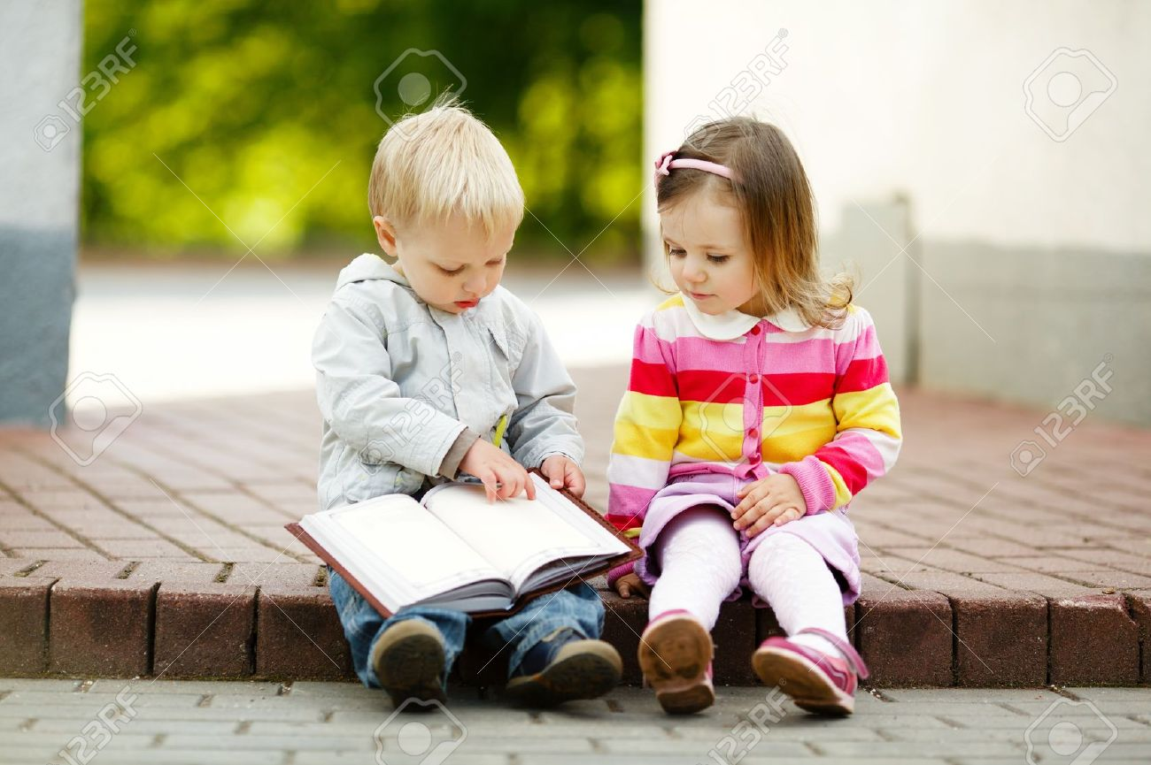 Cute Boy And Girl Reading A Book Stock Photo, Picture And Royalty